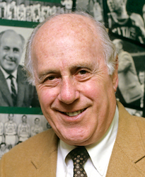 Boston Celtics President Red Auerbach in front of collage created by brother Zang Auerbach
